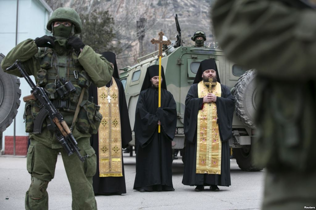 Orthodox monks pray next to armed servicemen near Russian army vehicles outside a Ukrainian border guard post in the Crimean town of Balaclava (Google Image)