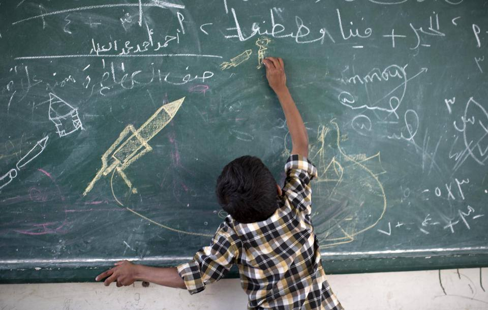 A Palestinian boys draws on the chalkboard at a UN school in the Gaza Strip - Photo courtesy of 'Shebab News Agency' Facebook page