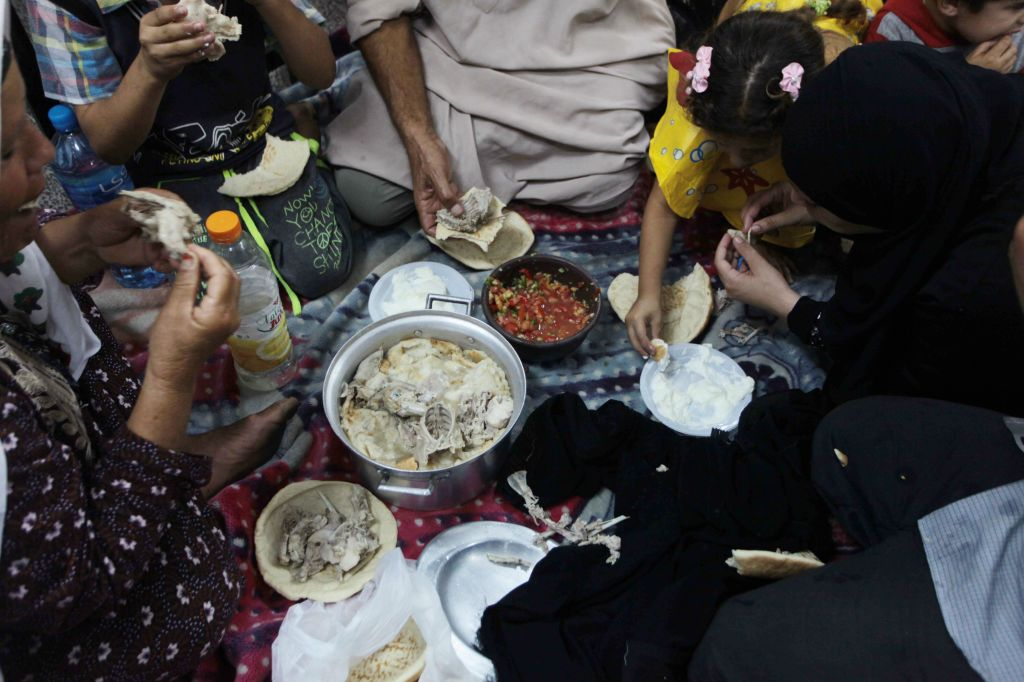 Many Palestinians sought shelter in UN schools. This photo depicts a Palestinian family breaking their fast while they shelter from Israeli shelling - Google Images