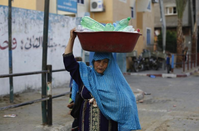 A Palestinian woman goes to fill water from a UN school - Google Images