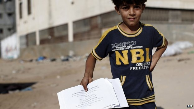 A Palestinian boy holds 'warning' leaflets dropped by the IDF - BBC