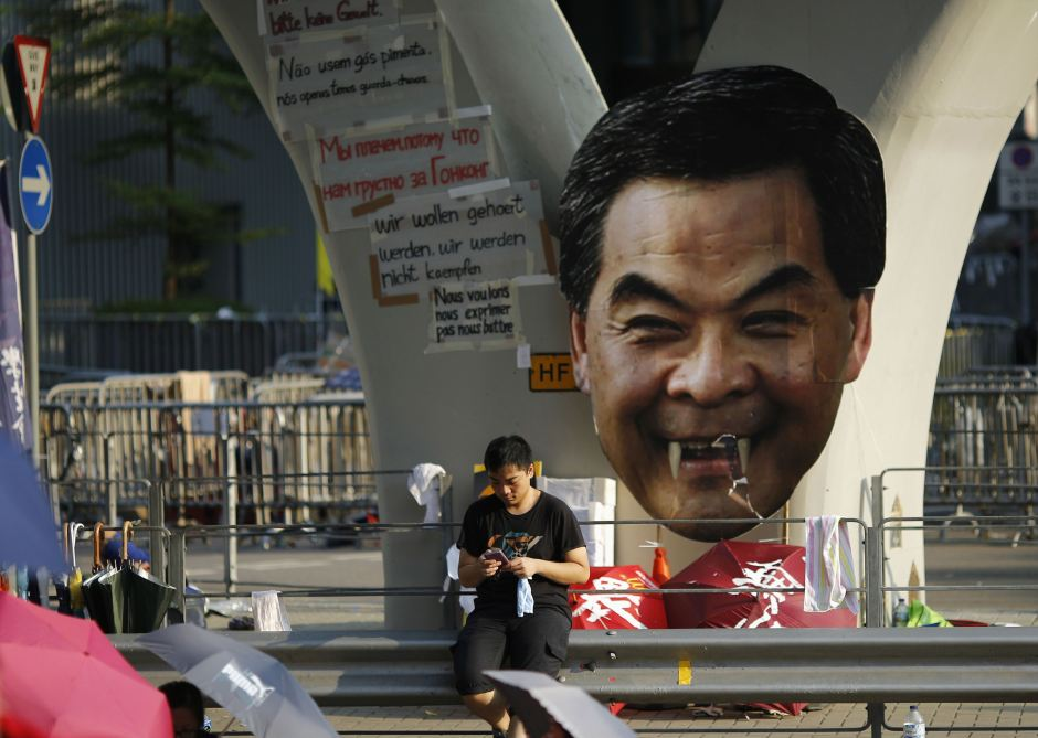 A protester sits next to a defaced cut-out of Hong Kong Chief Executive CY Leung while blocking a street outside the government headquarters in Hong Kong on Sept. 29 --- Reuters